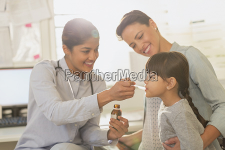 female pediatrician feeding cough syrup to