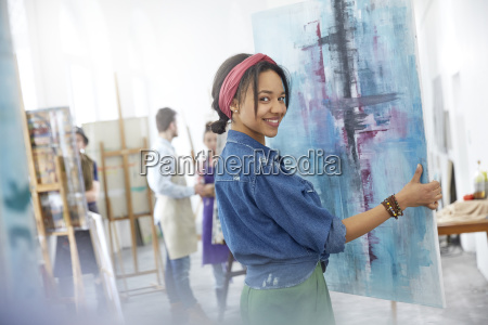 portrait smiling female artist lifting painting