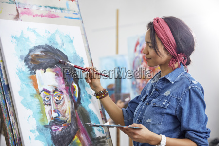 female artist painting in art studio