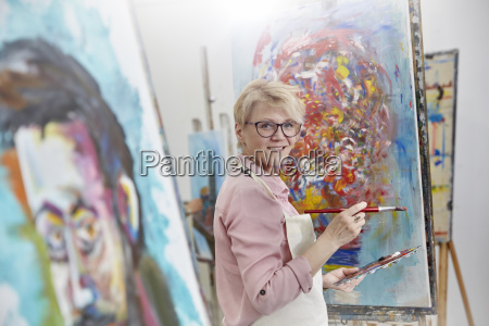portrait smiling female artist painting at
