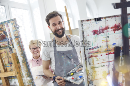 portrait smiling artists painting at easels