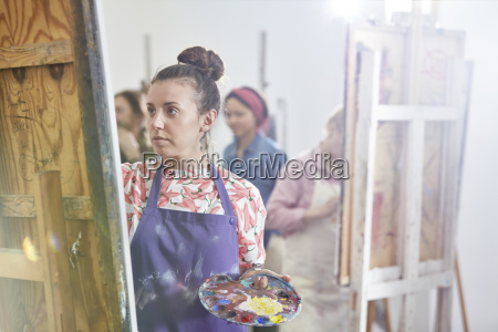 focused female artist with palette painting