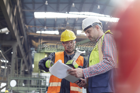 male foreman and worker with clipboard