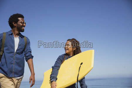 father and daughter carrying boogie board