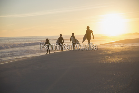 silhouette family surfers walking with surfboards