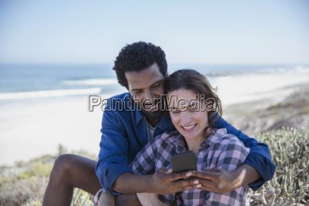 smiling multi ethnic couple taking selfie