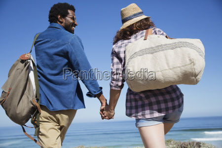 multi ethnic couple holding hands walking