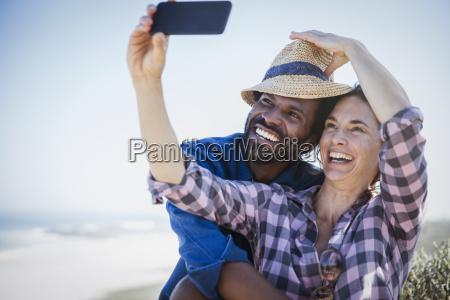 playful smiling multi ethnic couple taking