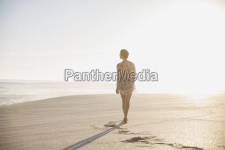 pensive serene woman walking on sunny