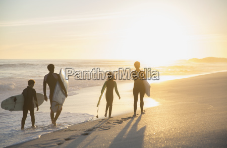 family surfers walking with surfboards on