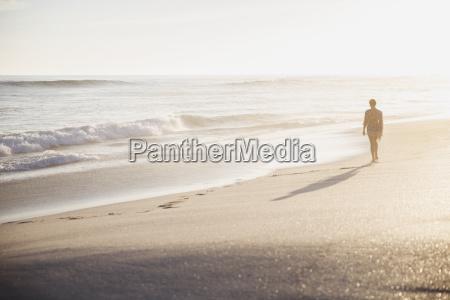silhouette woman walking on idyllic sunny