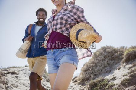 smiling enthusiastic couple walking on sunny
