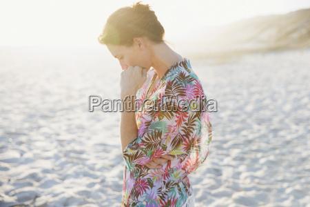 serene brunette woman in swimsuit coverup