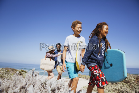 family walking with boogie boards on