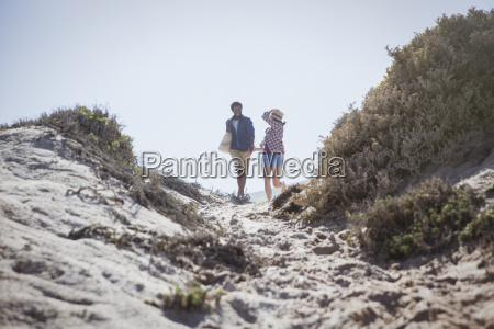couple walking on sunny summer beach