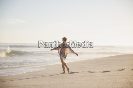 carefree woman walking with arms outstretched