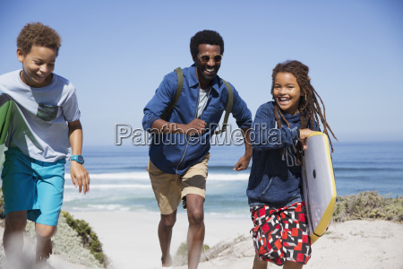 playful family with boogie board running