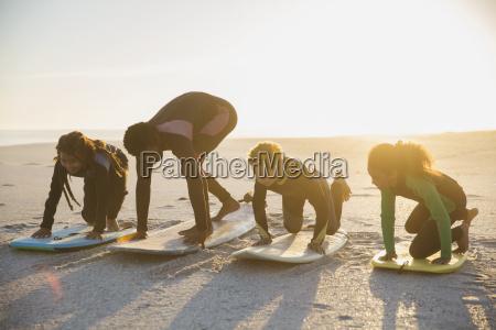 father surfer teaching children surfing on