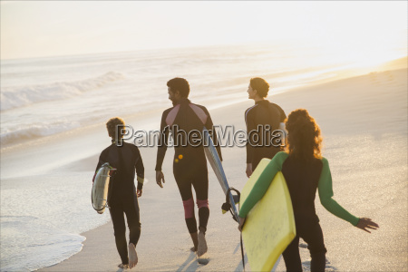 family walking carrying surfboards and boogie