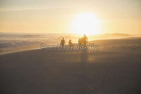 silhouette family walking on sunny summer