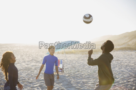 father and children playing soccer on