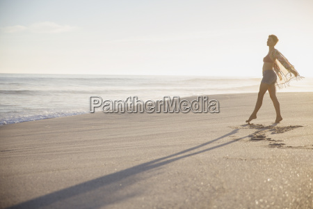 carefree woman walking on sunny summer