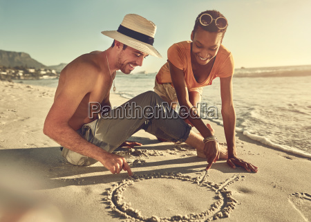 young couple drawing in sand on