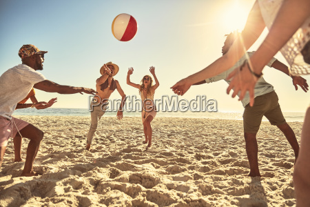playful young friends playing with beach