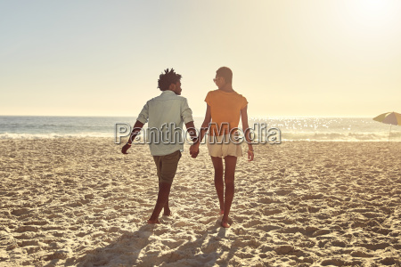 young couple holding hands walking on