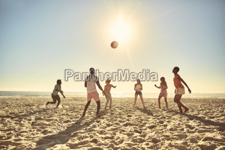 young friends playing with beach ball