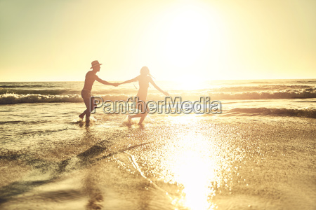 young couple holding hands walking in