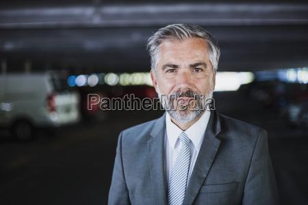 portrait of confident businessman in parking