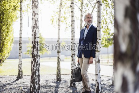 businessman holding bag leaning against a