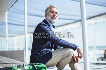 businessman sitting outdoors with bag