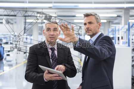 two businessmen looking at graphic on