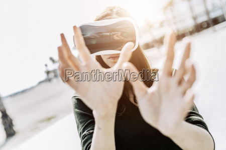 young woman wearing vr glasses outdoors
