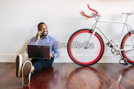 smiling man on cell phone sitting