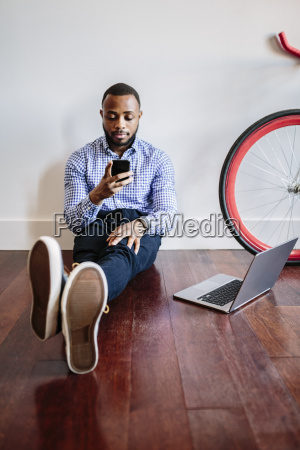 man sitting on wooden floor with