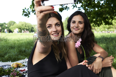 friends taking smartphone selfies in the