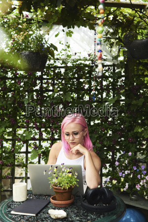 young woman with pink hair using