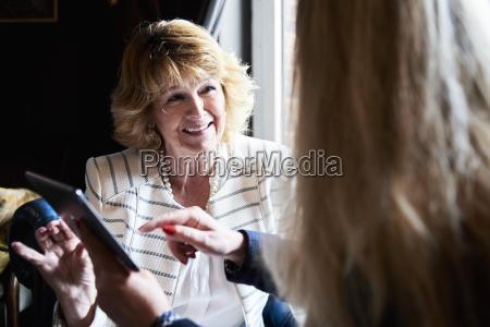 two senior businesswomen with tablet having