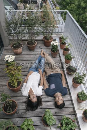 relaxed, couple, lying, on, balcony - 23351799