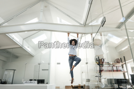 young woman hanging on beam in