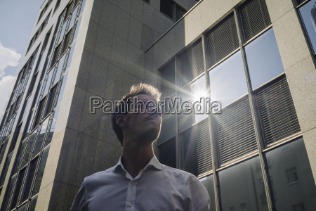businessman standing outdoors with sun reflecting