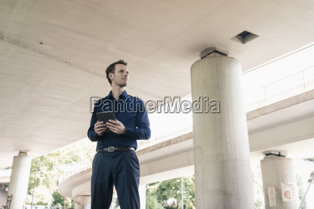 businessman standing at underpass holding tablet