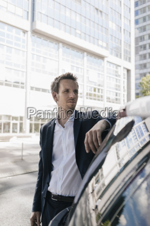 businessman standing next to car with