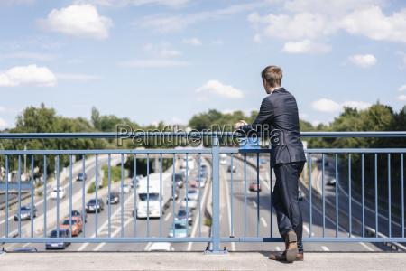 businessman standing on a bridge over