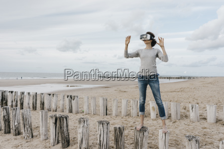 woman standing on wooden stakes on