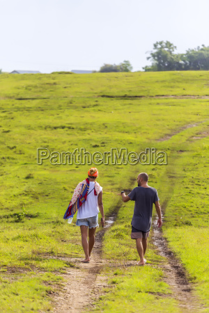 back view of couple walking barefoot