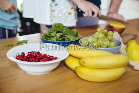 close up of family cutting fruit